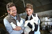 Cheerful couple of breeders in barn with goats