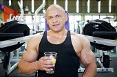 Bodybuilder in black jersey sits on exercise machine and holds glass with water with lemon in gym ha