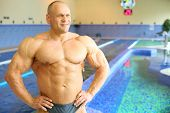 Happy bodybuilder in swimming trunks looks away near pool of gym hall