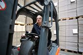 Forklift driver inside a forklift, manipulating a joystick in a warehouse full of pallets empty, pla