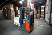 Reach truck is piling up pallets in a low section of the warehouse