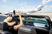 image of terminator  - Woman in convertible waving hand to pilot and stewardess against private jet at airport terminal - JPG
