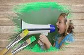 Composite image of little girl with bullhorn against wooden surface with paintbrushes