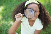 Young girl looking through magnifying glass in the park on a sunny day