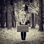 Girl With Vintage Suitcase And Camera Standing In Forest And Looking Up