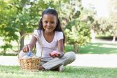 Little girl sitting on grass counting easter eggs smiling at camera on a sunny day