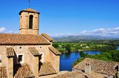 Esglesia Vella Church and Ebro River in Miravet, Spain with the Serra de Cardo mountain range in the background