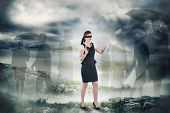 Redhead businesswoman in a blindfold against stormy sky with tornado over landscape