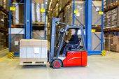 Reach truck forklift driving past an isle in a warehouse at speed. A panned image, with stock and ca