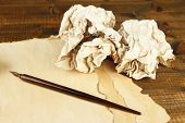Crumpled paper balls with ink pen and envelopes on wooden background