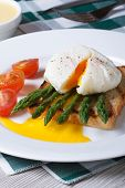 stock photo of benediction  - Toast with asparagus eggs Benedict and tomato on white plate closeup - JPG