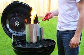 Man starting BBQ fire with lighter