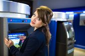 Pretty, young woman withdrawing money from her credit card in at an ATM (shallow DOF; color toned im
