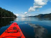 picture of beep  - A red kayak on the calm blue waters of the ocean harbour on a bright sunny day with fluffy white clouds reflecting in the beep blue water - JPG