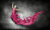 Young attractive woman in pink dress jumping high