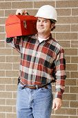 Handsome repairman carries his tool box on his shoulder.
