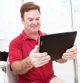 Man reading a tablet pc while using the bathroom.