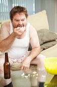 Middle aged man at home on the couch watching tv, drinking beer, and eating popcorn, in his underwea