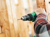 Closeup of a carpenter's hands using a drill on a construction site.  Focus on drill and hand.  Shal