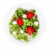 Green salad made with  arugula, tomatoes, cheese mozzarella balls and sesame  on plate, isolated on