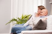 Mature Couple Watching Tv On The Sofa