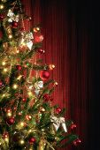 Half Christmas tree next to red window curtains with copy space