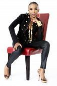 Young Beautiful African Woman Sitting on Red Chair, Wearing a Black Jacket, Golden Jewellery and Pin
