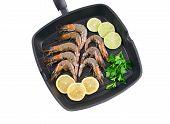 Raw shrimps on frying pan.