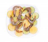 Raw shrimps on sliced lemon and lime.