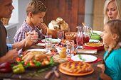 Portrait of modern family praying before festive dinner