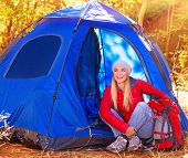Happy woman enjoying time spending in camp, sitting near blue tent in autumn park, active youth, travel and tourism concept