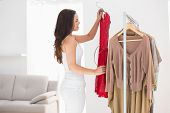 Pretty brunette picking out red dress at clothes store