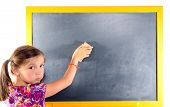 A Little Girl With Pigtails Writes On A Blackboard