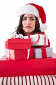 Confused brunette holding pile of gifts on white background