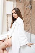 Image of beautiful young woman dressed in bathrobe