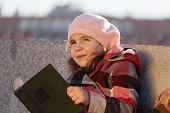Girl in a pink beret reads the book