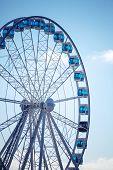 Ferris Wheel Above Blue Sky Background