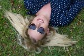 image of splayed  - Lovely young lady relaxing on the grass and wearing heart shaped sunglasses - JPG