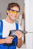 Smiling repairman with drill