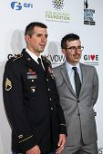 NEW YORK, NY - NOVEMBER 05: Brian McGough, Staff Sergeant, US Army, Veteran (L) and comedian John Oliver attend Stand Up For Heroes at Madison Square Garden on November 5, 2014 in New York City.