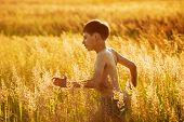 stock photo of beatitudes  - Happy boy running in a field of high grass - JPG