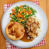 Steak pie served with mash and mixed vegetables.
