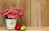 Tin pot of pink flowers with yellow and red pears by wooden background