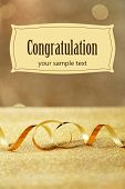 Serpentine ribbon on table on golden shiny background