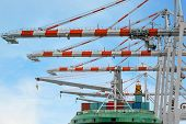 Container Ship In Terminal Working With Shore Crane At Dock