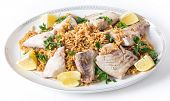 Lebanese-style fried fish on a serving dish with caramelised onion flavoured rice and roasted almond slivers.