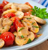 stock photo of sauteed  - Sauteed mushrooms with tomatoes on blue plate - JPG