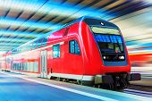 stock photo of passenger train  - Scenic view of red modern high speed passenger commuter double decker train on tracks at the station platform with motion blur effect - JPG