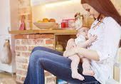 picture of breastfeeding  - Mother breastfeeding her little baby girl in her arms - JPG