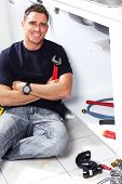 stock photo of plumber  - Plumber man with tools in the kitchen - JPG